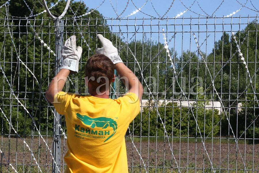 Установка сетки колючей Пиранья на забор